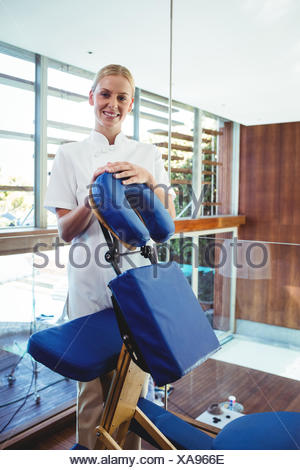 Portrait of masseuse next to massage chair - Stock Photo