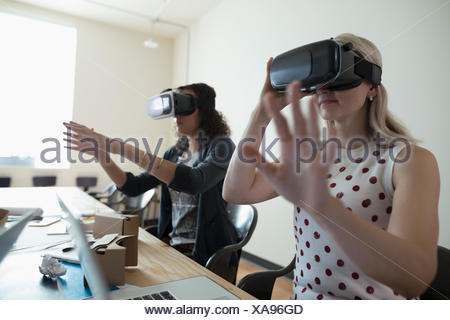 Female computer programmer designers testing virtual reality simulator glasses in office - Stock Photo