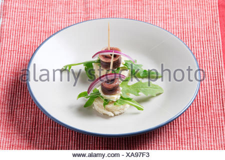 Anchovy canapes garnished with arugula and onion - Stock Photo