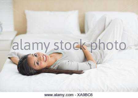Young girl lying on bed looking at camera - Stock Photo