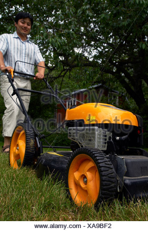 Low angle view of an Asian man using the lawn mower against trees - Stock Photo