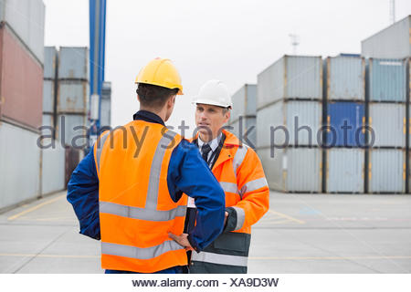 Workers conversing in shipping yard