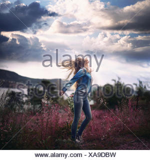 Carefree woman standing in a meadow, Norway - Stock Photo