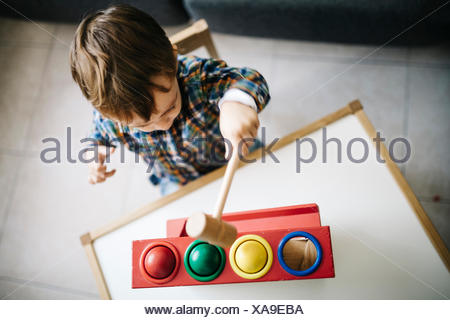 Little boy playing with wooden motor skill toy - Stock Photo