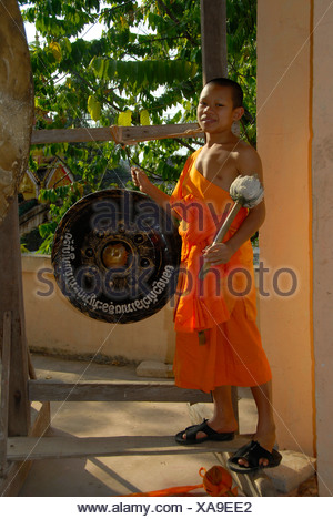 Buddhist novice monk wearing an orange robe hitting a gong, Wat Phonxay, Vientiane, Laos, Southeast Asia - Stock Photo