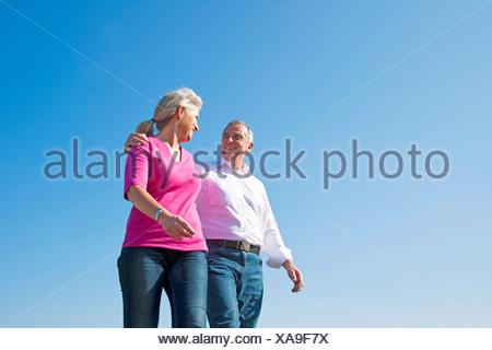 Couple walking under blue sky - Stock Photo