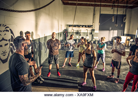 Trainer talking to fitness class in gym - Stock Photo