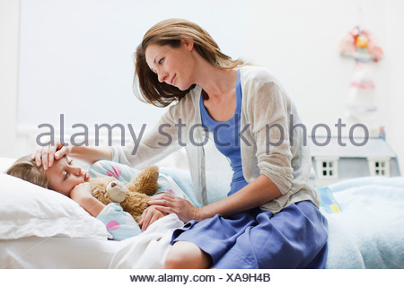 Mother checking on sick daughter laying in bed - Stock Photo