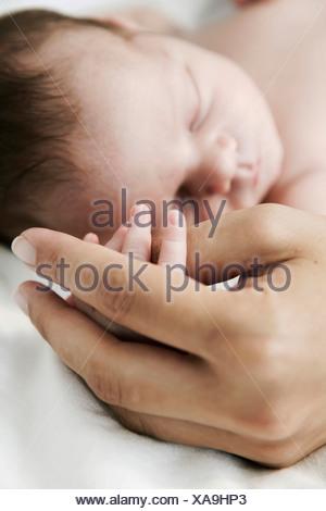 Mother holding hand of her sleeping newborn son - Stock Photo