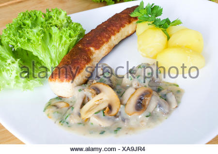Grilled sausage on potatoes and mushrooms - Stock Photo