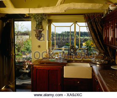 Old fashioned Belfast sink beneath window in country style kitchen with open door and cream painted rustic ceiling beams - Stock Photo