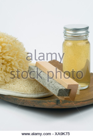Grooming products, pumice stone, body oil, loofah and sponge on wooden tray - Stock Photo