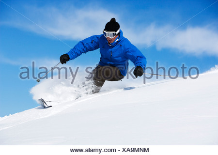 Man in blue & black outfit turning. - Stock Photo
