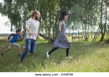 Playful family running in rural yard - Stock Photo