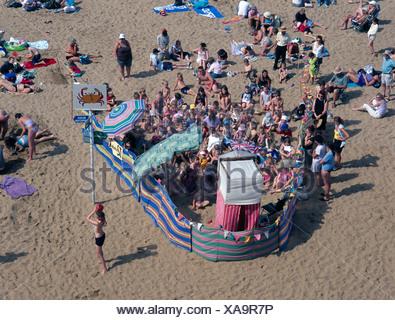 Children watching Punch Judy show on beach Viking Bay Broadstairs Kent UK - Stock Photo