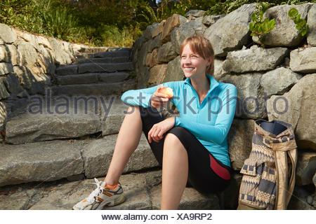 Mid adult female runner taking a break in park eating an apple - Stock Photo