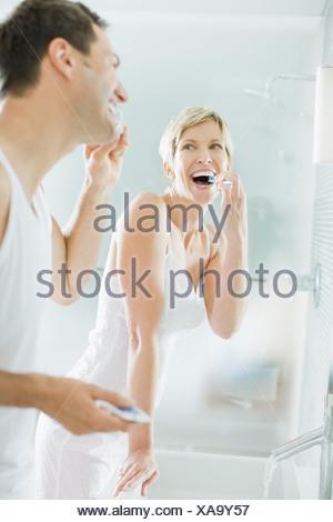 Couple brushing teeth in bathroom - Stock Photo