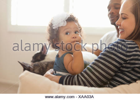 Mother and father sitting with young daughter - Stock Photo