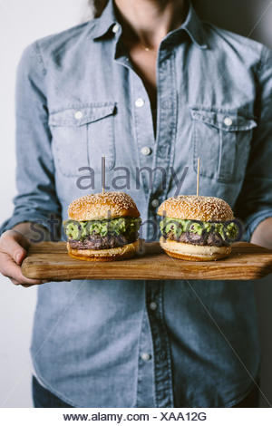 A woman is photographed from the front view while holding two guacamole burgers in her hand on a wood cutting board. - Stock Photo