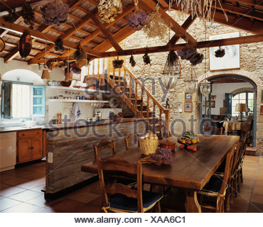Rustic wooden table and chairs in dining area of large Spanish kitchen with dried flowers hanging from wooden ceiling beams - Stock Photo