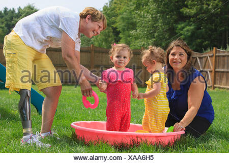 Grandmother with a prosthetic leg playing with her grandchildren on a child's pool - Stock Photo