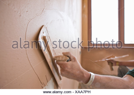 Man plastering wall with trowel - Stock Photo