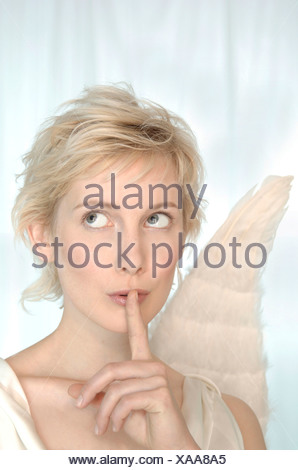 Blonde woman with angel wings making a silence gesture, looking mysterious - Stock Photo