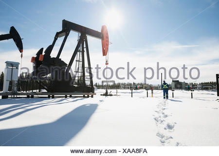Worker walking toward drilling rigs in snow - Stock Photo