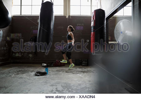 Female boxer jumping rope behind punching bags in gym - Stock Photo