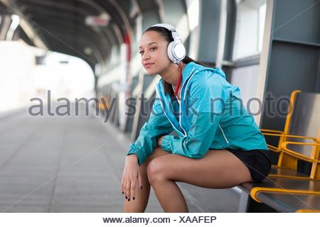 MODEL RELEASED. Young woman sitting on railway platform wearing headphones. - Stock Photo