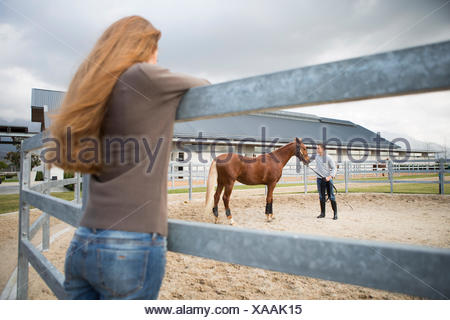 Young woman watching stablehand train horse in paddock ring - Stock Photo