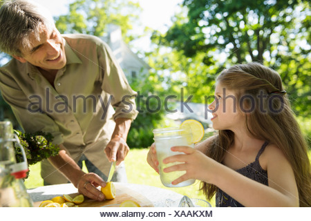 On the farm. Children and adults working together. A girl and an adult man making lemonade. Cutting up fresh fruits. - Stock Photo