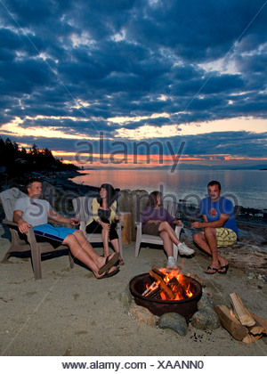 After beautiful summer day friends relax around - Stock Photo