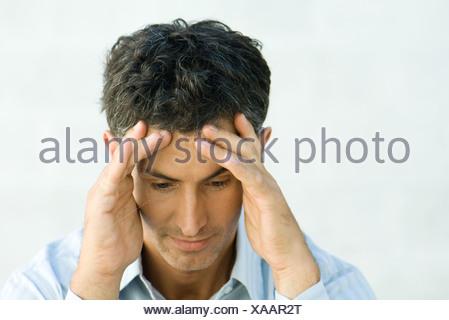 Man, holding head, portrait - Stock Photo