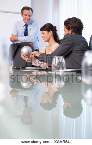 Business people in conference room with sphere - Stock Photo