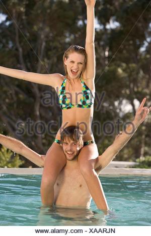 A teenage couple having fun in a swimming pool - Stock Photo