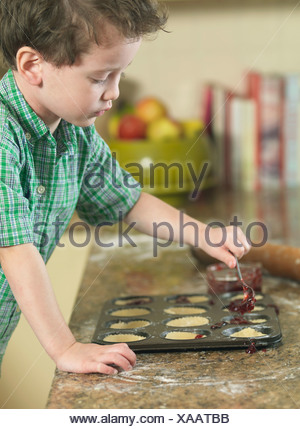 Boy spooning batter into pan in kitchen - Stock Photo