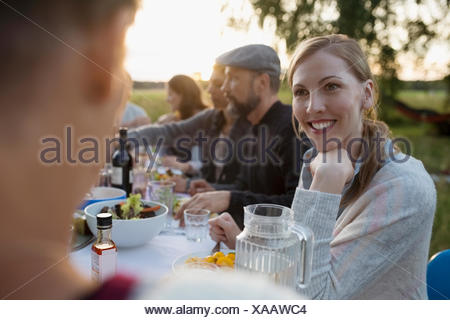 Smiling woman talking to friend, enjoying garden party dinner - Stock Photo