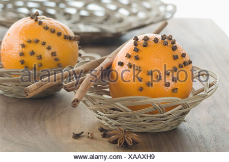Orange studded with cloves and cinnamon stick in basket besides star anise on table - Stock Photo