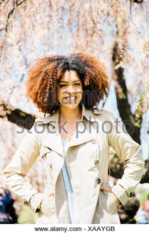 Portrait of mid adult woman, hands in pockets, looking at camera, smiling - Stock Photo
