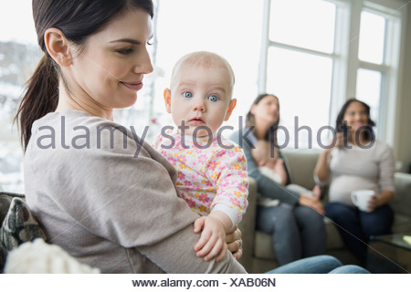 Mother holding curious baby in living room - Stock Photo
