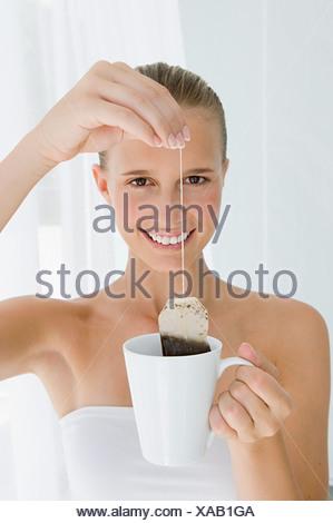Young woman holding tea bag - Stock Photo