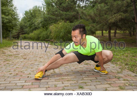 Young male runner crouching and stretching in park - Stock Photo
