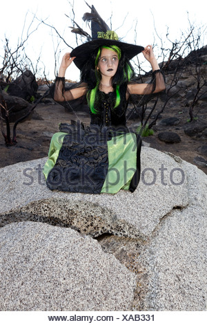 Little young girl costumed as witch sitting on rock looking away - Stock Photo