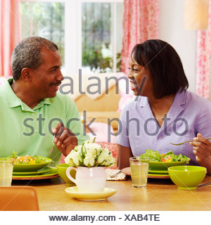 Mature couple eating salad and looking at each other - Stock Photo