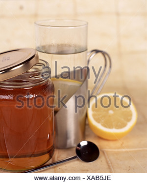 Silver mug steamed glass containing hot water and a lemon slice next to half opened jar of honey half a lemon and a silver - Stock Photo