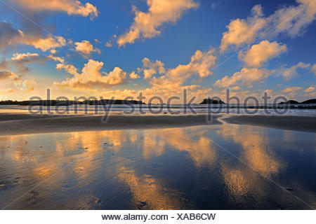 Clouds reflected in the Pacific Ocean at sunrise on Mackenzie Beach Pacific Rim NAtional Park British Columbia Canada - Stock Photo