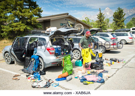 A backpacker prepares his gear before a hike. - Stock Photo