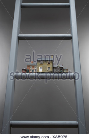 Small model houses on ladder - Stock Photo