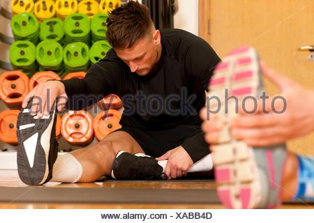 Man at gym sitting doing leg stretching exercises - Stock Photo